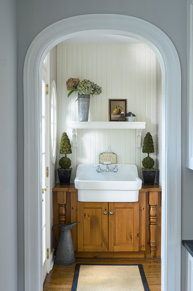 Inspiration for a small country powder room remodel in New York with recessed-panel cabinets, medium tone wood cabinets, wood countertops, white walls and brown countertops