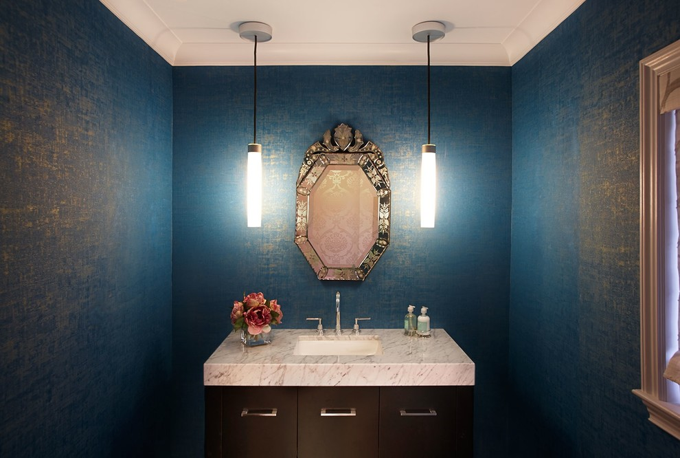 Mid-sized transitional powder room photo in New York with an undermount sink, flat-panel cabinets, dark wood cabinets, marble countertops and blue walls