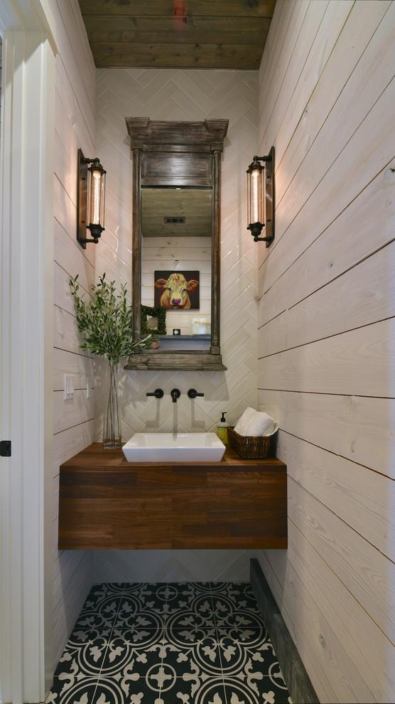 Idee per un bagno di servizio country con piastrelle beige, piastrelle di pietra calcarea, pareti beige, pavimento in cementine, lavabo a bacinella, top in legno, pavimento multicolore e top marrone