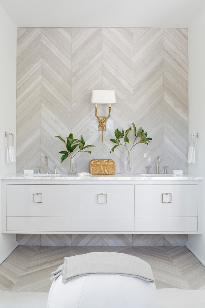 Example of a trendy powder room design in Atlanta with an undermount sink, marble countertops and beige walls