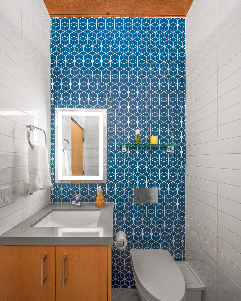 Example of a 1950s ceramic tile, white tile and blue tile powder room design in Los Angeles with flat-panel cabinets, medium tone wood cabinets, a wall-mount toilet, blue walls, an undermount sink and gray countertops