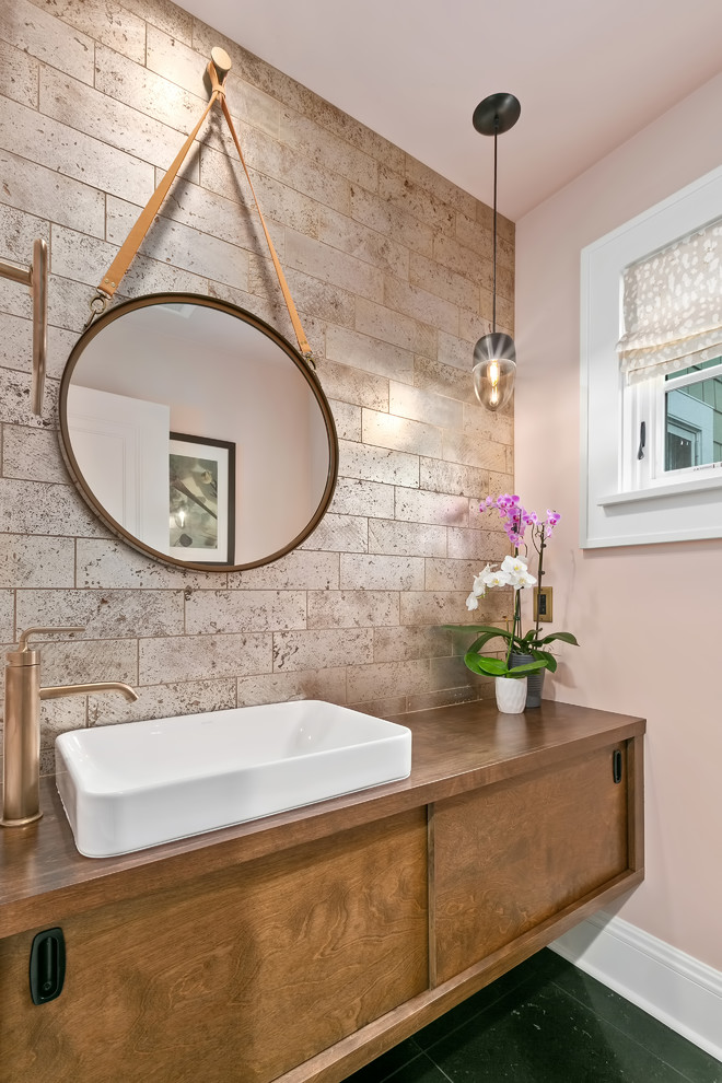 Example of a small transitional slate floor and black floor powder room design in Minneapolis with flat-panel cabinets, medium tone wood cabinets, pink walls, a vessel sink, wood countertops and brown countertops