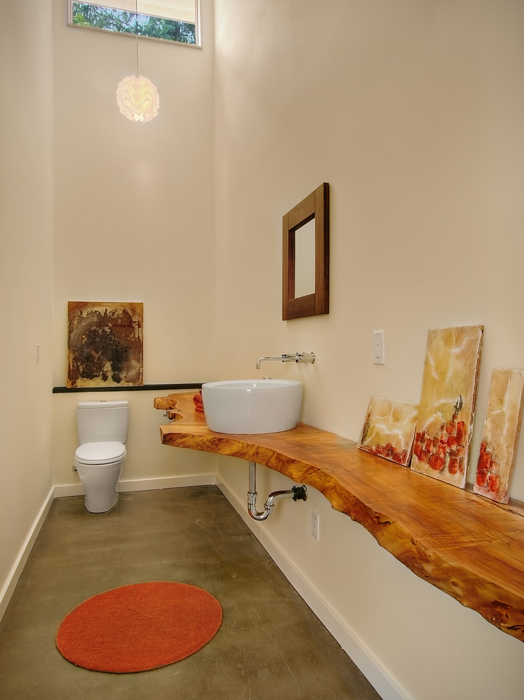 Inspiration for a contemporary concrete floor powder room remodel in Seattle with a vessel sink, wood countertops and brown countertops