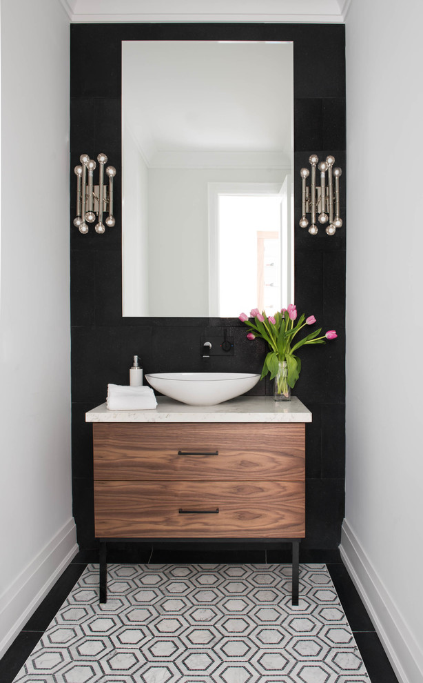 Example of a trendy powder room design in Toronto with flat-panel cabinets, medium tone wood cabinets, a vessel sink, marble countertops, black walls and beige countertops