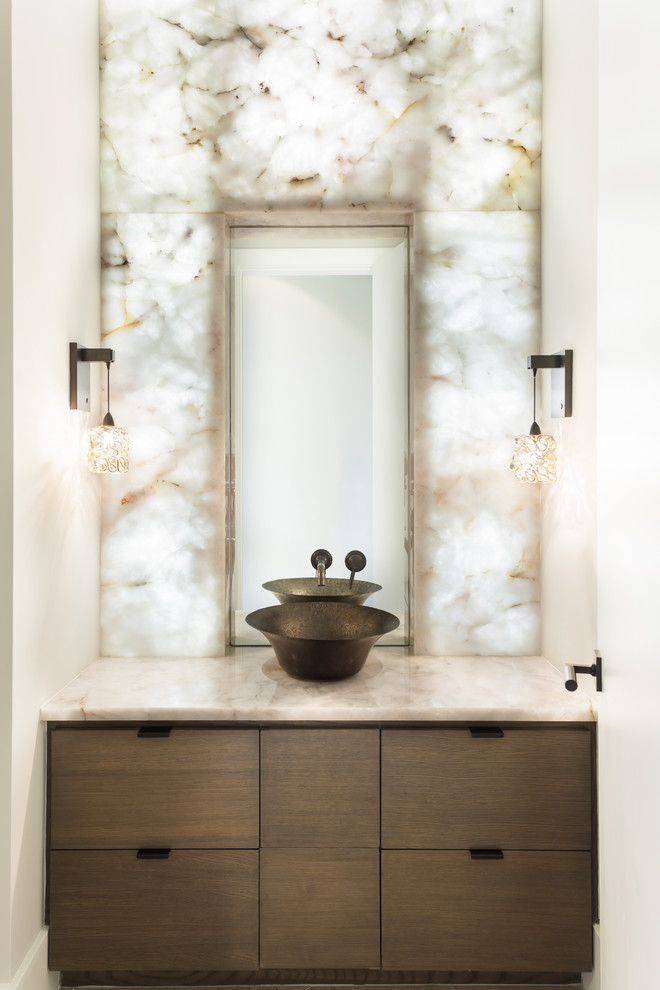 Inspiration for a contemporary white tile and stone slab powder room remodel in Houston with a vessel sink, flat-panel cabinets, dark wood cabinets, white walls and beige countertops