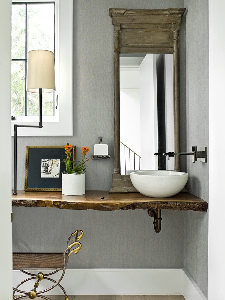 Inspiration for a cottage brown floor powder room remodel in Chicago with gray walls, a vessel sink, wood countertops and brown countertops