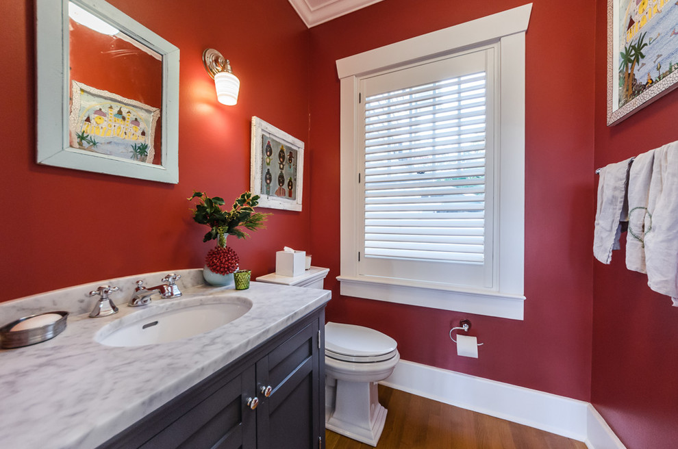 Powder room - traditional medium tone wood floor and brown floor powder room idea in Tampa with recessed-panel cabinets, black cabinets, red walls, an undermount sink and gray countertops