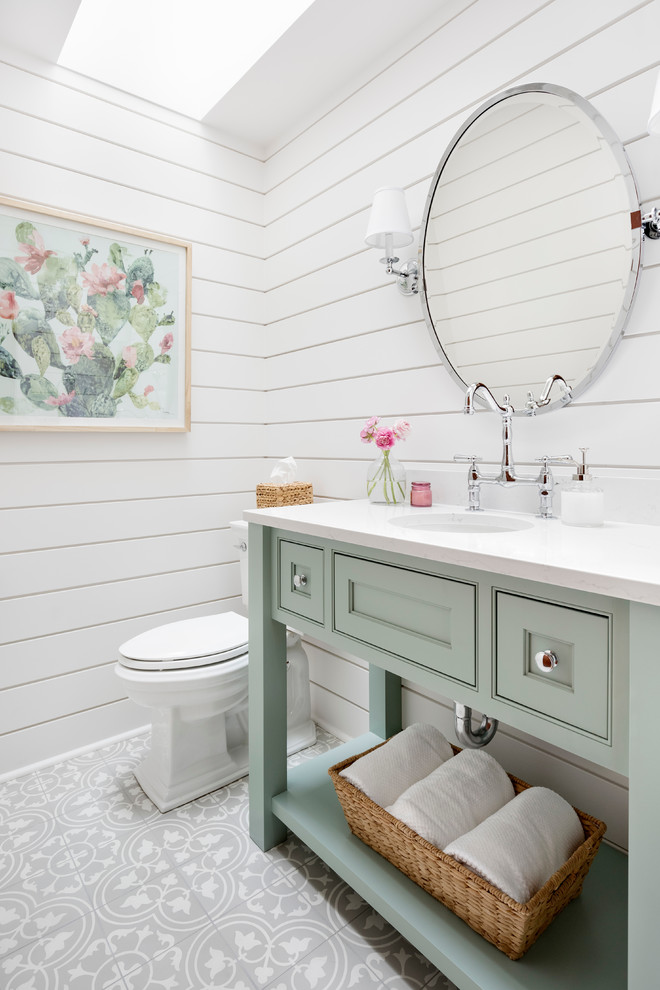 Inspiration for a country gray floor powder room remodel in Seattle with beaded inset cabinets, green cabinets, a two-piece toilet, white walls, an undermount sink and white countertops