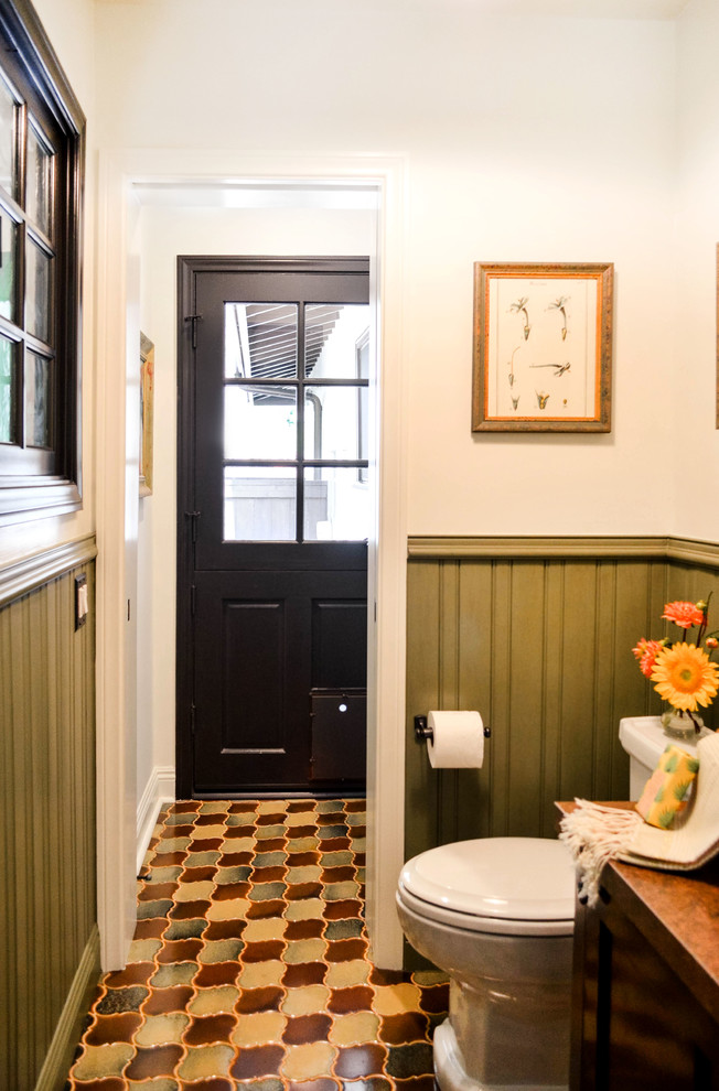 Small tuscan green tile ceramic tile and multicolored floor powder room photo in Los Angeles with furniture-like cabinets, dark wood cabinets, a one-piece toilet, white walls, a vessel sink, copper countertops and brown countertops