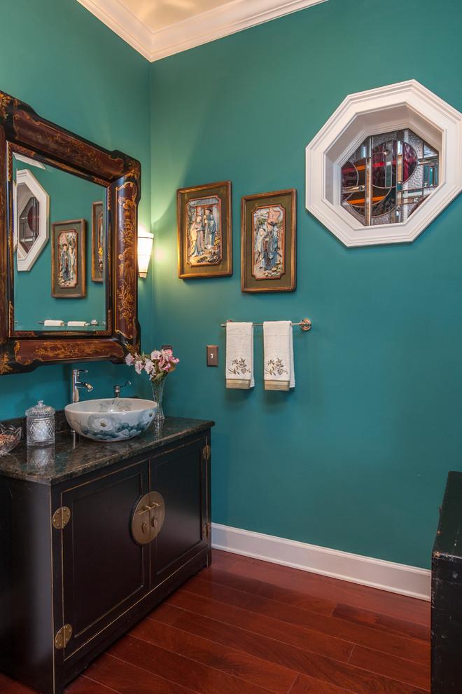 Ispirazione per un bagno di servizio etnico di medie dimensioni con lavabo a bacinella, consolle stile comò, ante nere, top in granito, pareti blu e pavimento in legno massello medio