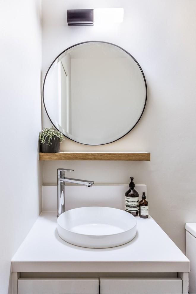 Cette photo montre un WC et toilettes tendance avec un placard à porte shaker, un carrelage gris, des carreaux de miroir, un mur gris et une vasque.