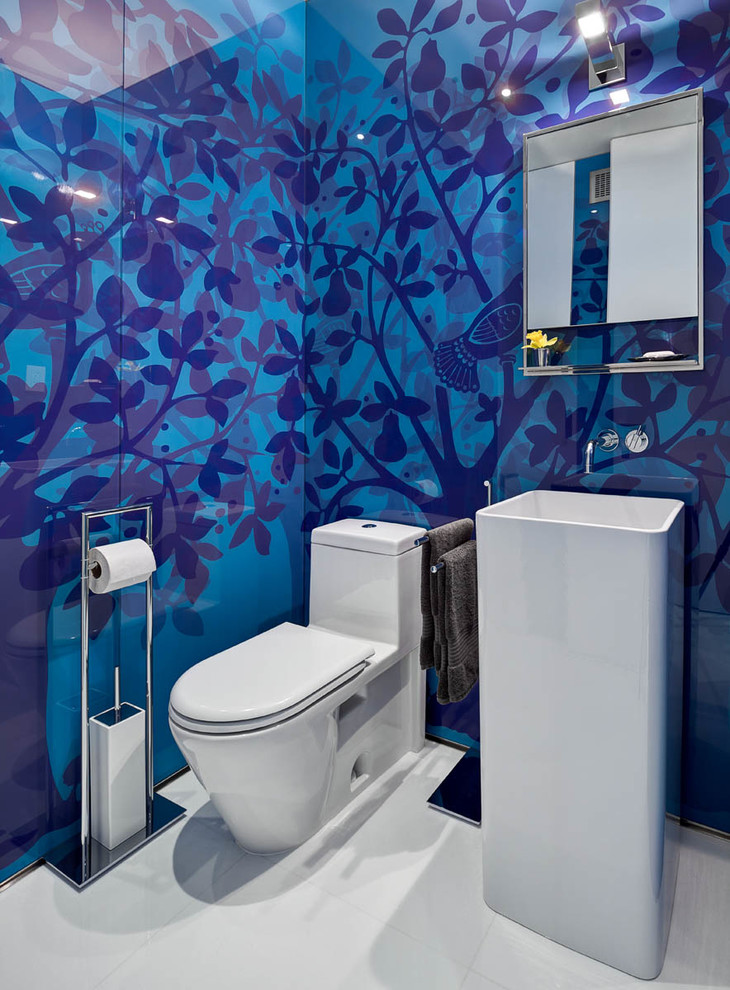 Example of a mid-sized trendy porcelain tile and white floor powder room design in New York with a pedestal sink, a one-piece toilet and blue walls