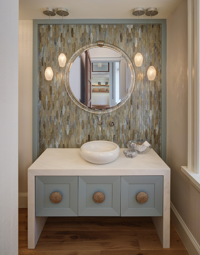 Powder room - mid-sized coastal multicolored tile and mosaic tile medium tone wood floor powder room idea in Miami with blue cabinets, a vessel sink, furniture-like cabinets, marble countertops and white countertops