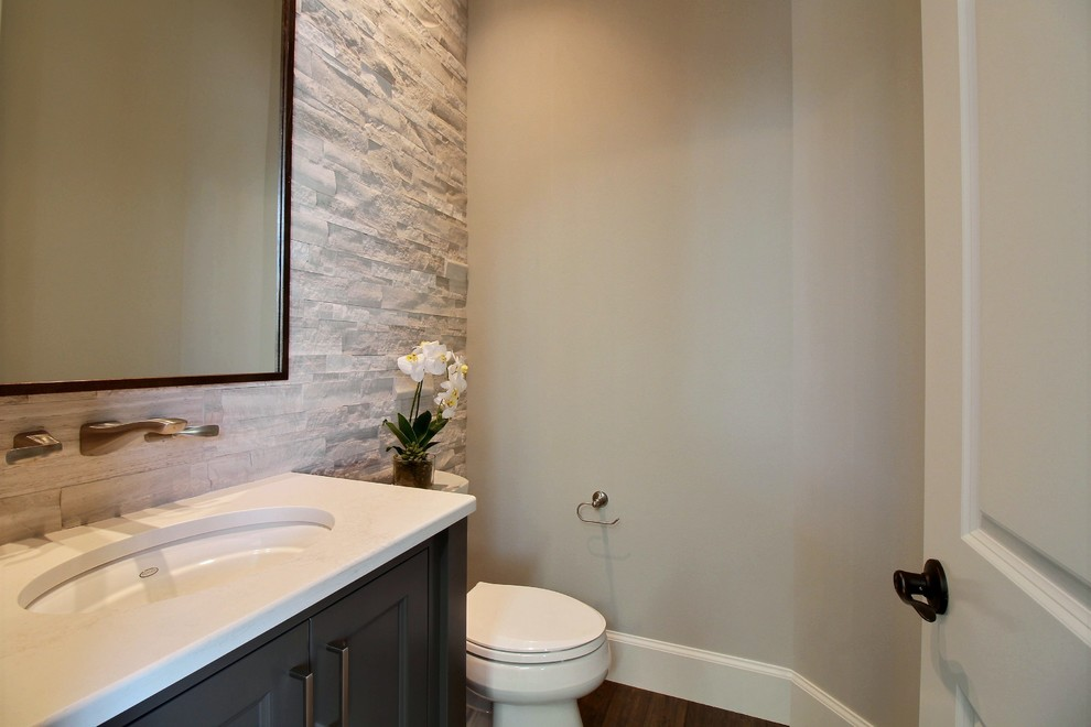 Powder room - mid-sized craftsman multicolored tile and ceramic tile ceramic tile and gray floor powder room idea in Portland with recessed-panel cabinets, dark wood cabinets, a two-piece toilet, gray walls, an undermount sink, quartz countertops and white countertops
