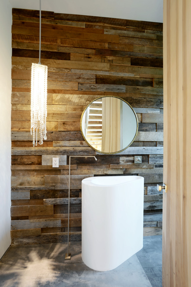 Mid-sized trendy concrete floor powder room photo in Los Angeles with a pedestal sink and brown walls