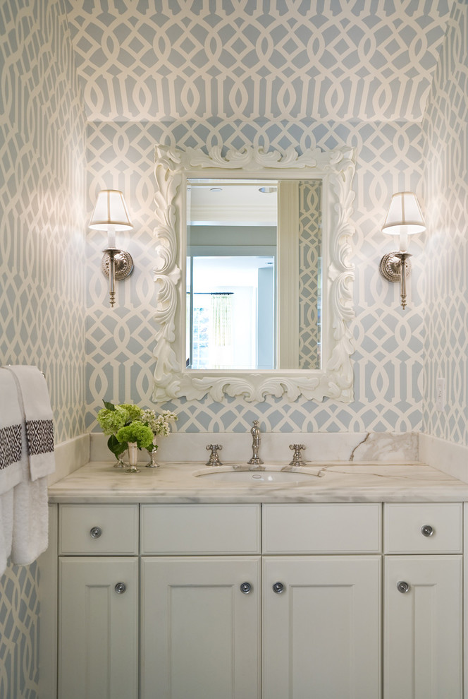 Inspiration for a timeless powder room remodel in Seattle with an undermount sink, recessed-panel cabinets, white cabinets, marble countertops and white countertops