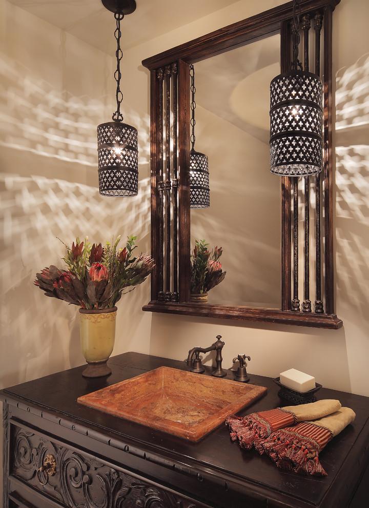 Powder room - mediterranean powder room idea in Phoenix with a drop-in sink, dark wood cabinets, wood countertops and brown countertops