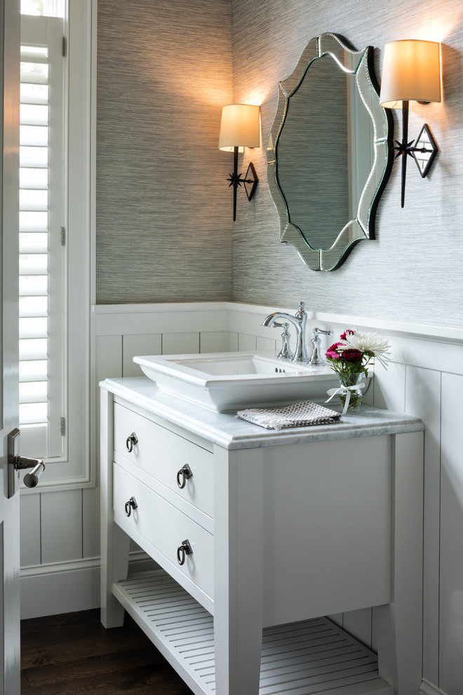 Beach style dark wood floor and brown floor powder room photo in Minneapolis with furniture-like cabinets, white cabinets, gray walls, a vessel sink and white countertops