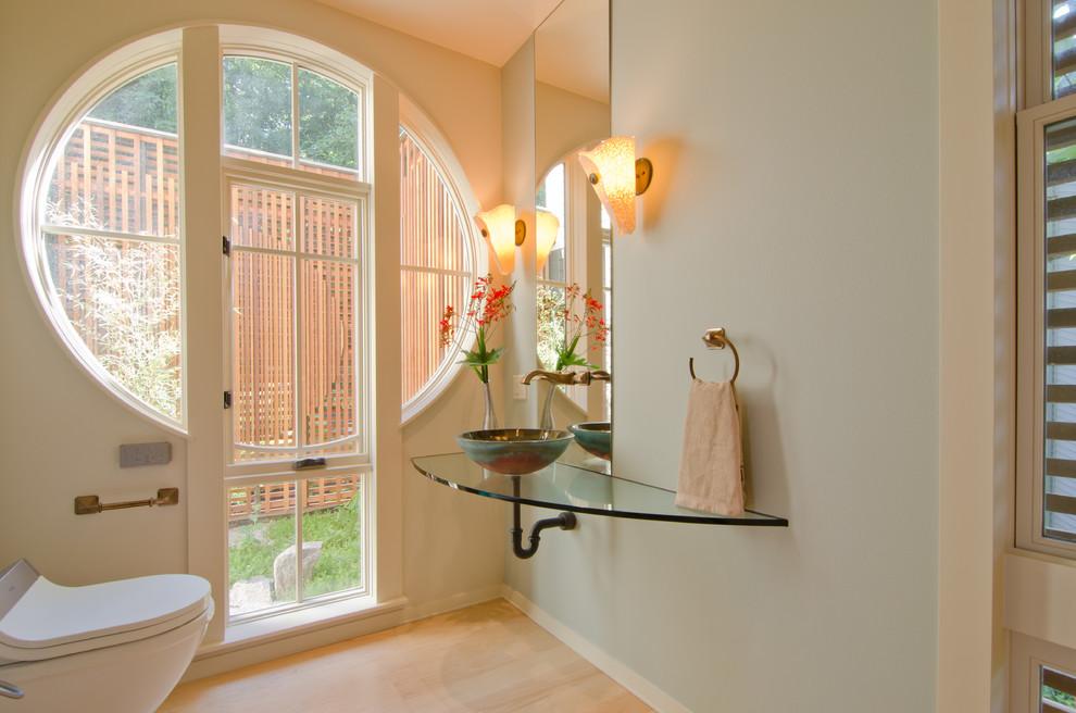 Foto di un bagno di servizio design di medie dimensioni con lavabo a bacinella, pareti blu, parquet chiaro, top in vetro e pavimento beige