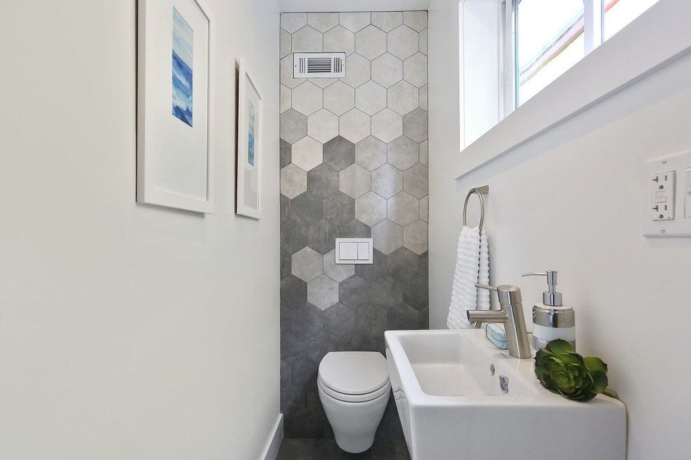 Powder room - small modern gray tile powder room idea in San Francisco with a wall-mount toilet, white walls and a wall-mount sink