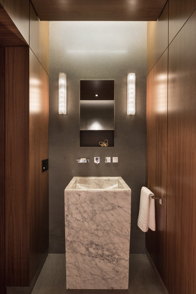 Example of a mid-sized minimalist gray tile powder room design in New York with a pedestal sink