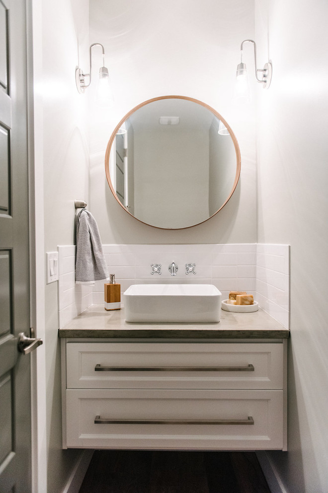 Inspiration for a small transitional powder room in Salt Lake City with furniture-like cabinets, white cabinets, white tile, subway tile, grey walls, ceramic floors, a vessel sink and concrete benchtops.