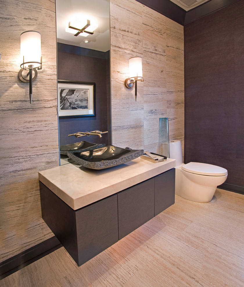 Example of a small trendy beige tile and porcelain tile porcelain tile and beige floor powder room design in Denver with a vessel sink, flat-panel cabinets, gray cabinets, a one-piece toilet, beige walls, quartz countertops and beige countertops
