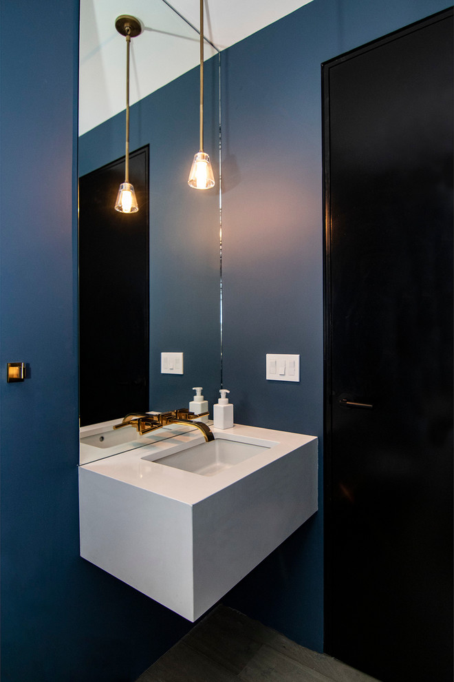 Example of a small trendy medium tone wood floor and gray floor powder room design in New York with blue walls, quartz countertops, white countertops and an undermount sink