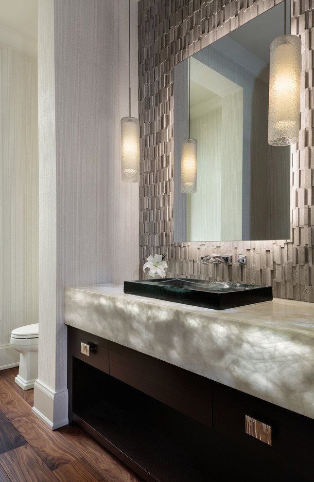 Inspiration for a mid-sized contemporary gray tile ceramic tile and brown floor powder room remodel in Miami with flat-panel cabinets, brown cabinets, onyx countertops, gray walls, a vessel sink and gray countertops