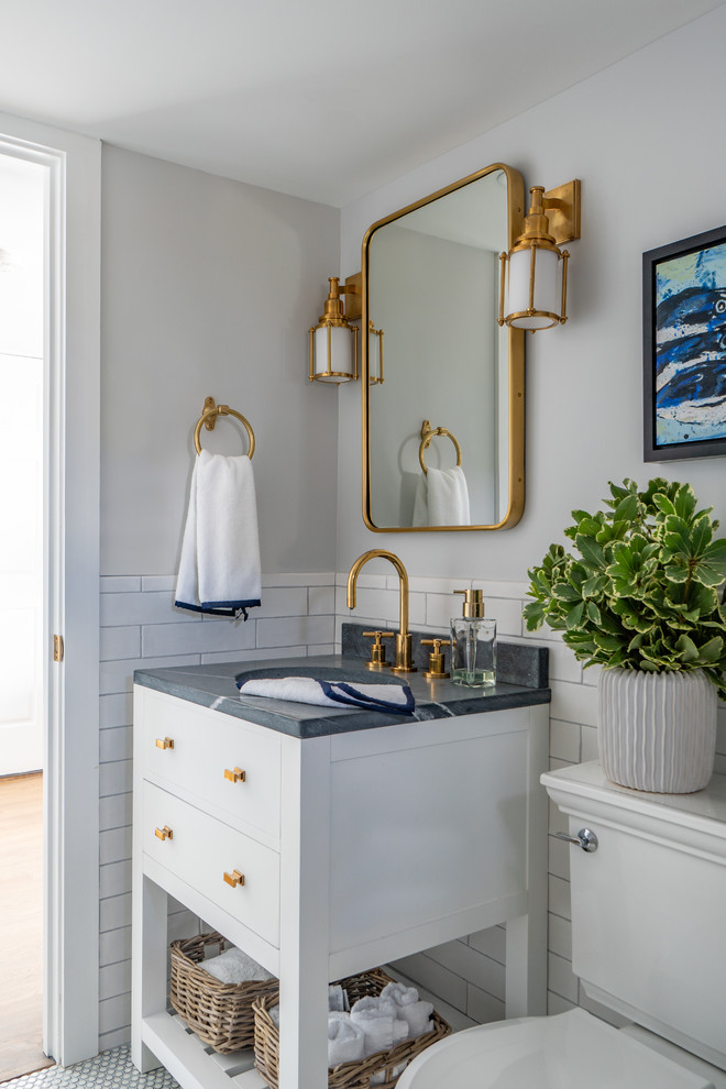 Powder room - small coastal white tile and subway tile mosaic tile floor and white floor powder room idea in Boston with furniture-like cabinets, white cabinets, a two-piece toilet, gray walls, an undermount sink, marble countertops and gray countertops