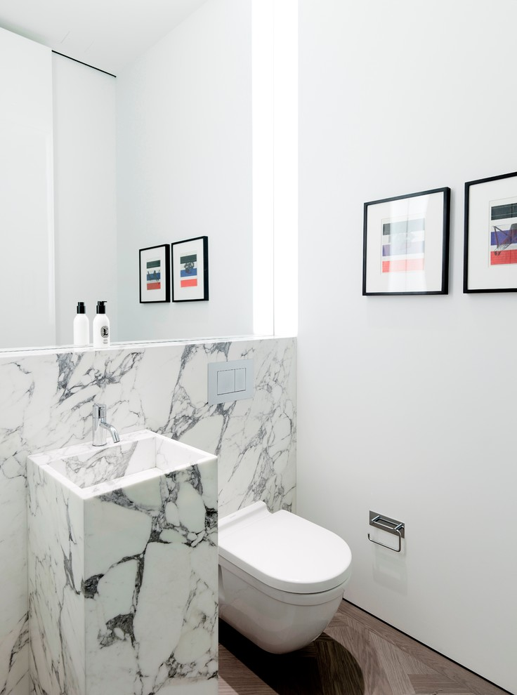 Example of a small trendy marble tile and white tile dark wood floor powder room design in New York with an integrated sink, a wall-mount toilet, white walls and marble countertops