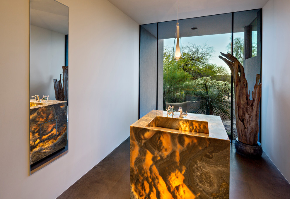 Inspiration for a southwestern concrete floor and gray floor powder room remodel in Phoenix with white walls, a pedestal sink and onyx countertops