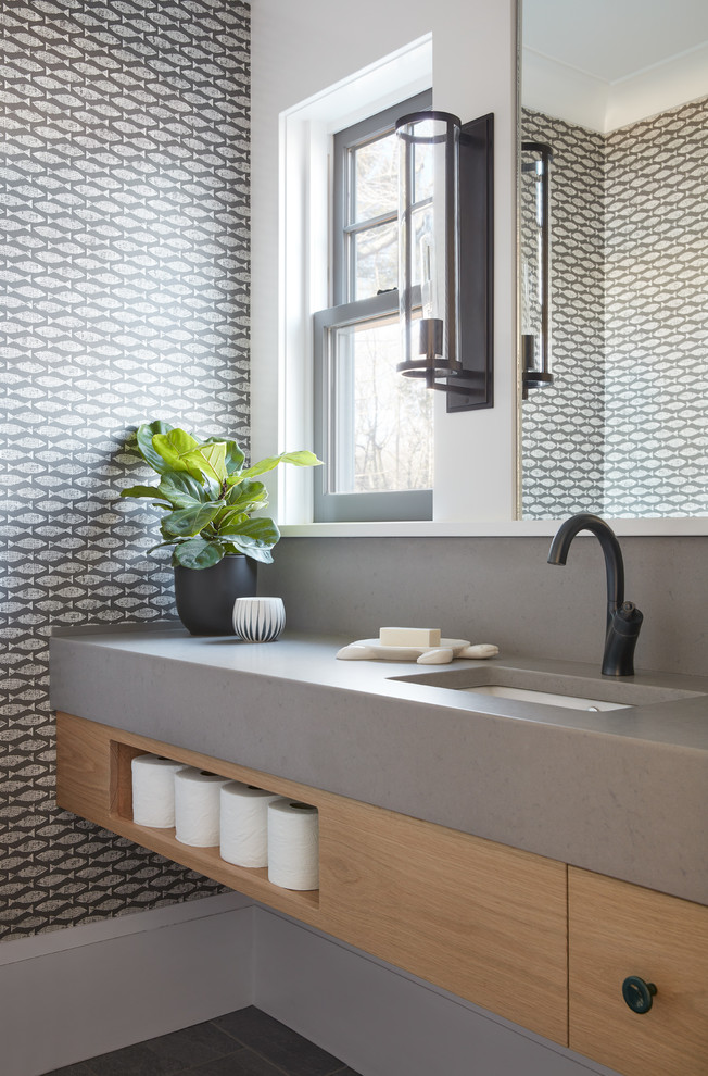 Beach style gray floor powder room photo in Manchester with flat-panel cabinets, light wood cabinets, multicolored walls, an undermount sink and gray countertops