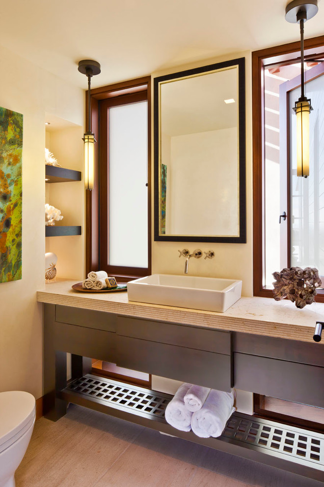 Inspiration for a contemporary beige tile limestone floor powder room remodel in Los Angeles with a vessel sink, dark wood cabinets, limestone countertops, beige walls and flat-panel cabinets