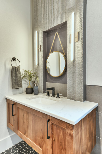 Powder room - mid-sized transitional gray tile gray floor and ceramic floor powder room idea in Austin with shaker cabinets, medium tone wood cabinets, white walls, an undermount sink and white countertops