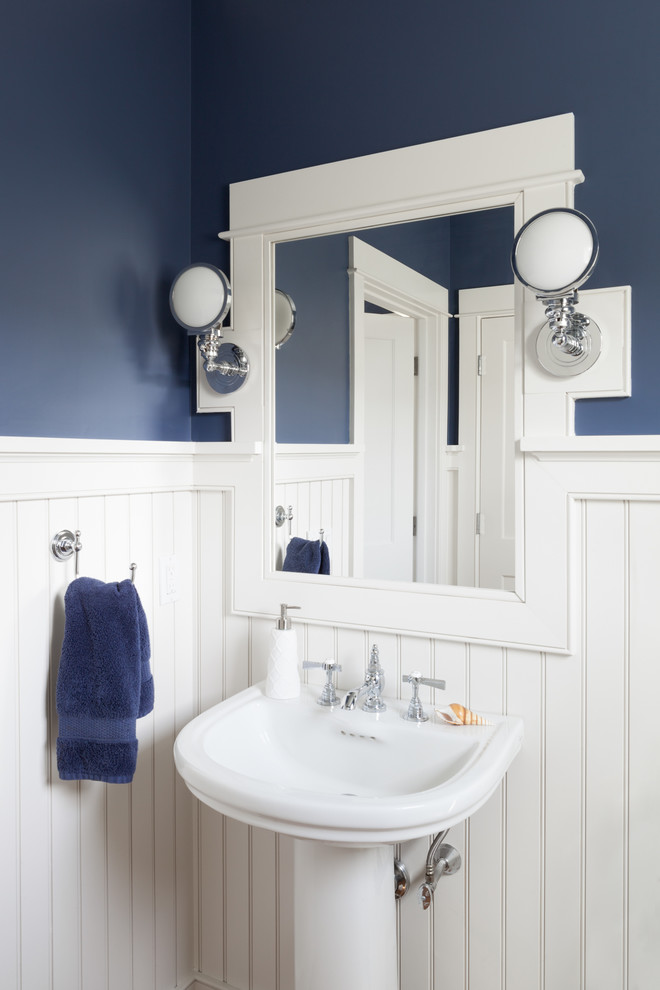 Small coastal medium tone wood floor and brown floor powder room photo in Boston with blue walls and a pedestal sink