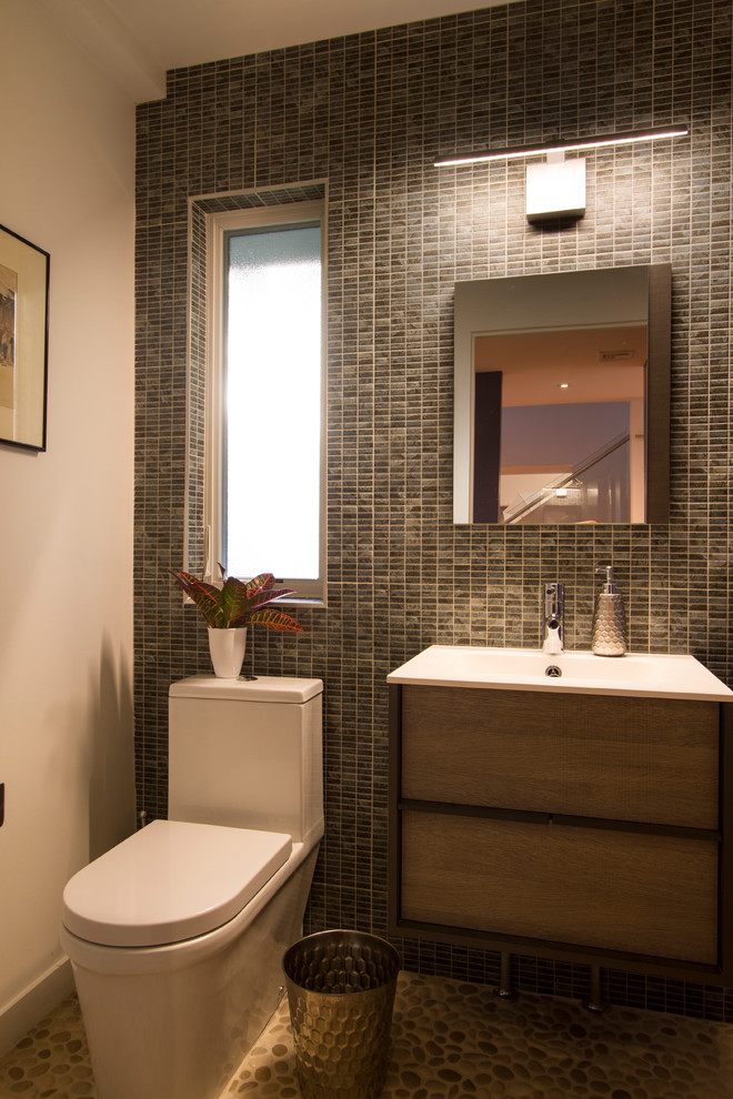 Small minimalist multicolored tile and porcelain tile pebble tile floor and beige floor powder room photo in New York with flat-panel cabinets, medium tone wood cabinets, a one-piece toilet, white walls, an integrated sink, solid surface countertops and white countertops
