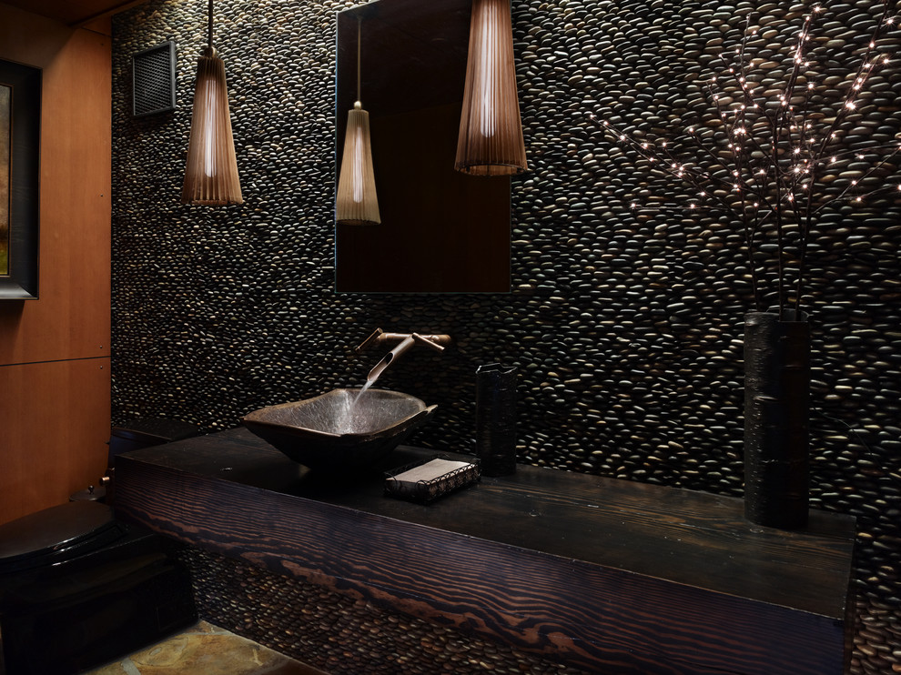 Inspiration for a rustic pebble tile powder room remodel in Seattle with a vessel sink, wood countertops and brown countertops
