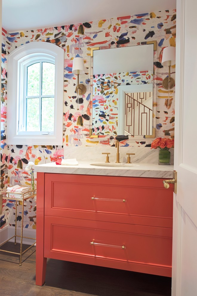 Small eclectic medium tone wood floor and brown floor powder room photo in Other with flat-panel cabinets, orange cabinets, an undermount sink and marble countertops