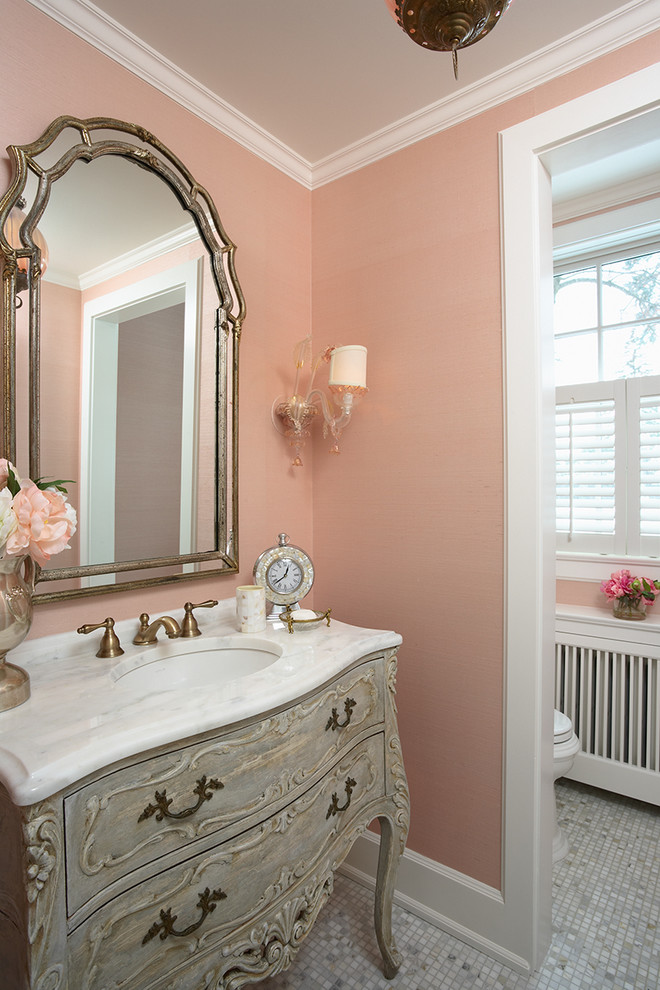 Powder room - mid-sized victorian white tile mosaic tile floor powder room idea in Minneapolis with pink walls, furniture-like cabinets, an undermount sink and marble countertops