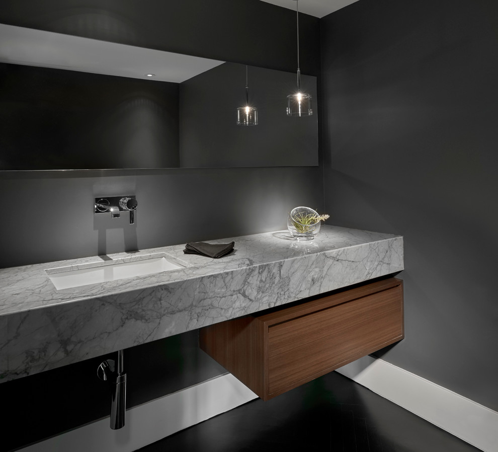 Example of a mid-sized trendy powder room design in Chicago with flat-panel cabinets, gray walls, dark wood cabinets, an undermount sink and gray countertops