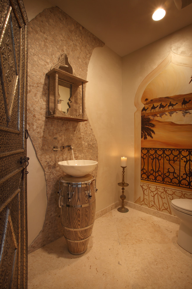 Powder room - mid-sized mediterranean beige tile and travertine tile ceramic floor powder room idea in Miami with beige walls and a vessel sink
