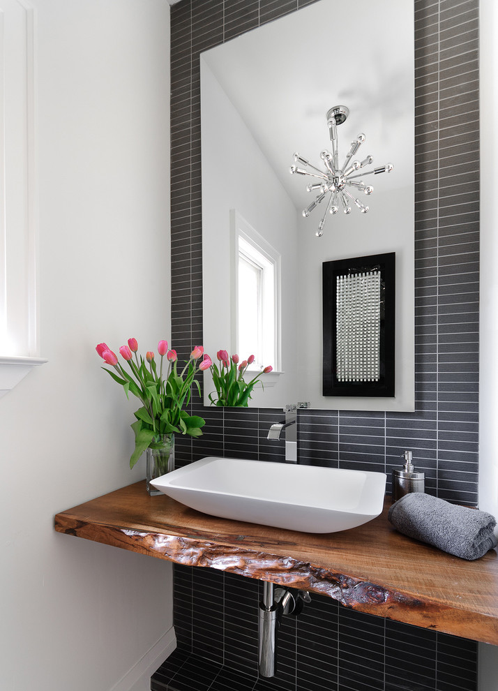 Example of a trendy powder room design in Toronto with a vessel sink and brown countertops