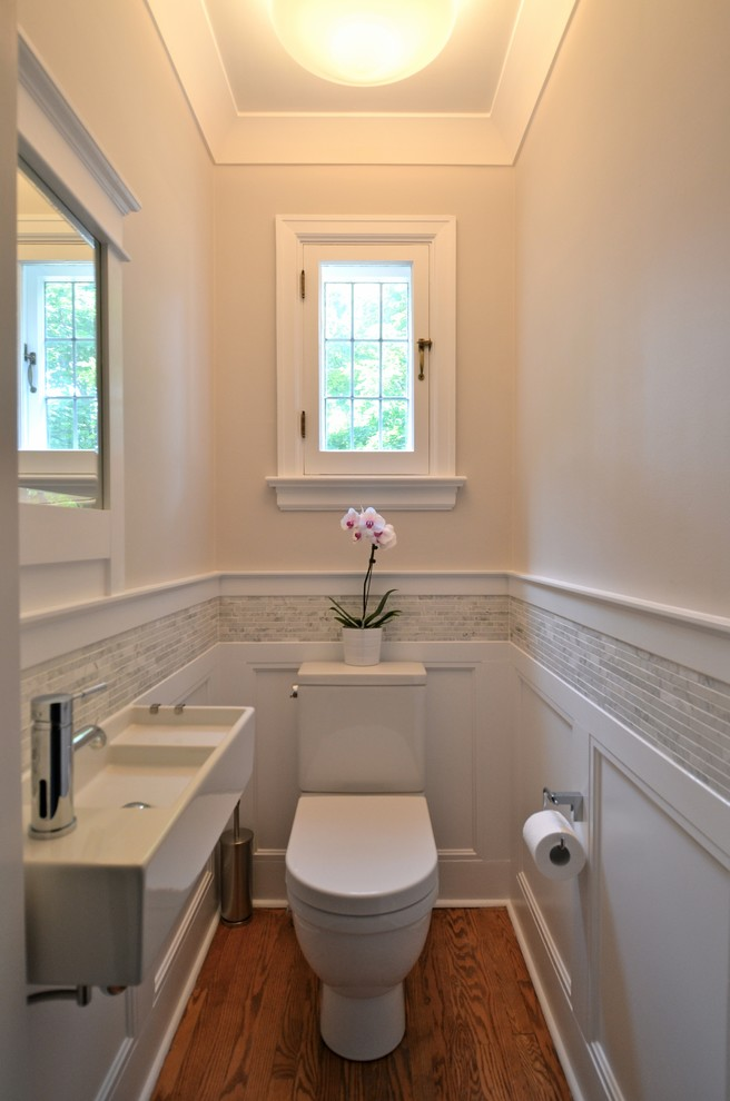 Example of a small classic gray tile and matchstick tile medium tone wood floor powder room design in Ottawa with a wall-mount sink, a two-piece toilet and beige walls