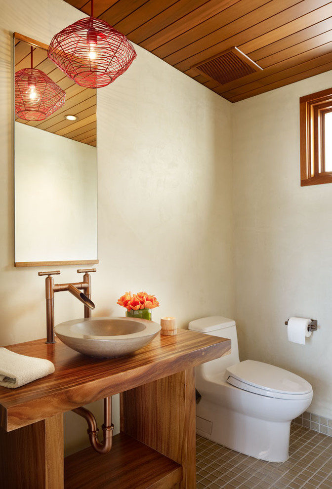Powder room - mid-sized tropical porcelain tile and brown floor powder room idea in Los Angeles with a vessel sink, open cabinets, dark wood cabinets, beige walls, wood countertops and brown countertops