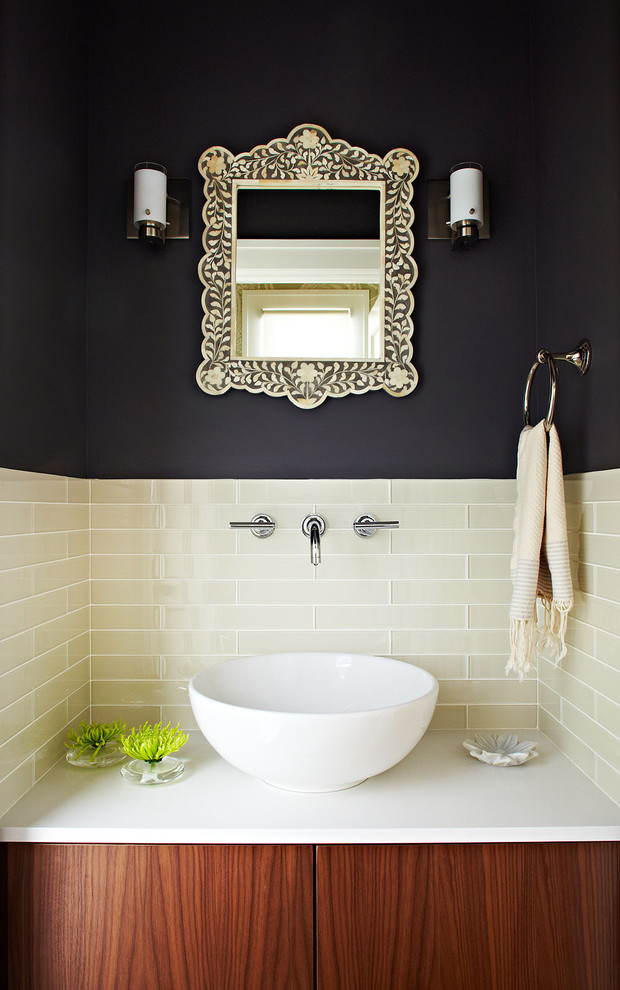 Small trendy beige tile powder room photo in San Francisco with a vessel sink, flat-panel cabinets, medium tone wood cabinets, engineered quartz countertops, black walls and white countertops