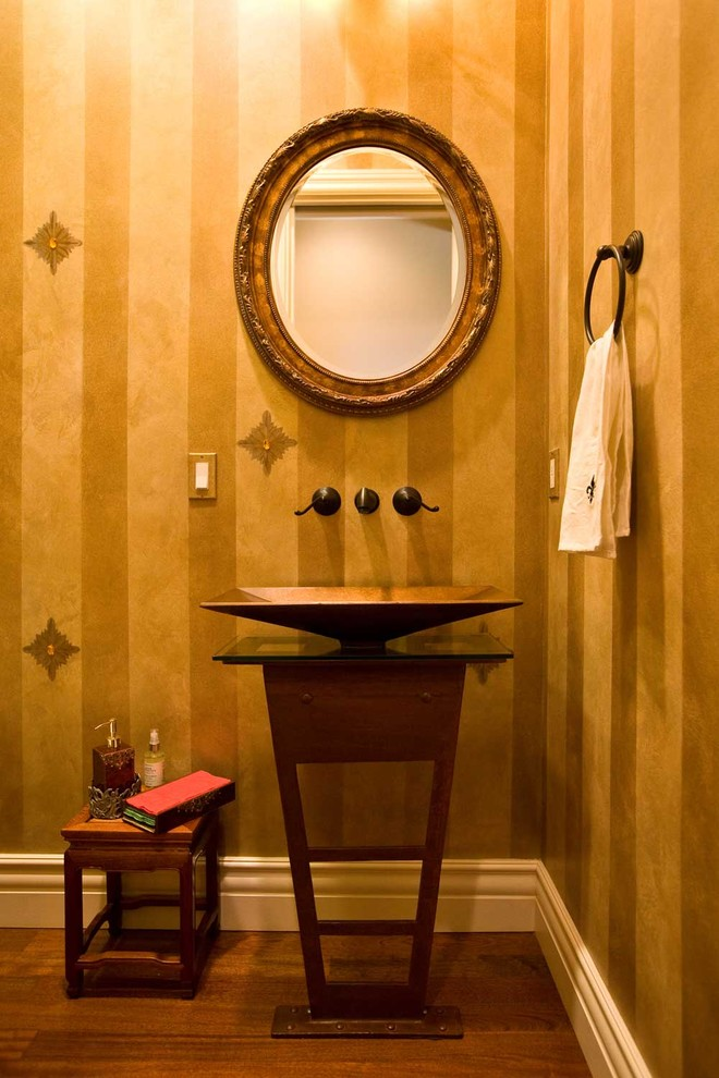 Inspiration for a mid-sized timeless yellow tile dark wood floor and brown floor powder room remodel in San Francisco with a vessel sink, furniture-like cabinets, dark wood cabinets, glass countertops, a one-piece toilet, yellow walls and brown countertops