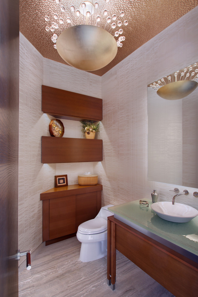 Trendy powder room photo in New York with a vessel sink, glass countertops and a one-piece toilet
