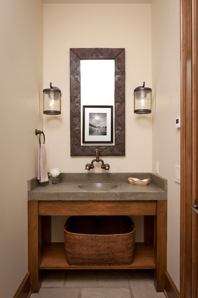 Mid-sized mountain style powder room photo in Other with an integrated sink, concrete countertops, beige walls and gray countertops