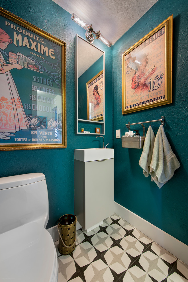 Example of a small eclectic porcelain tile and multicolored floor powder room design in Denver with a one-piece toilet, blue walls, flat-panel cabinets, gray cabinets and a console sink